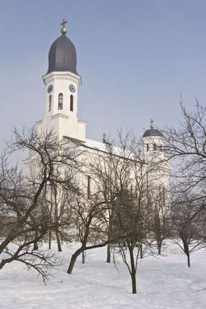 serbia landscape: view of traditional orthodox christian church and fruit orchard mid winter