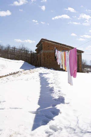 serbia landscape: colorful clothes hanging to dry in the snow