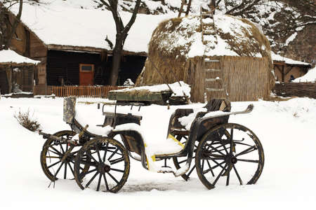 an old horse drawn carriage in the snow photo