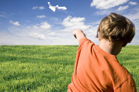 young boy flying a paper airplane Standard-Bild