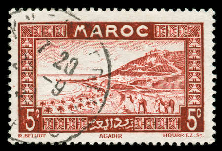 camel post: vintage stamp from Morocco depicting a traditional scenic view with camel riders