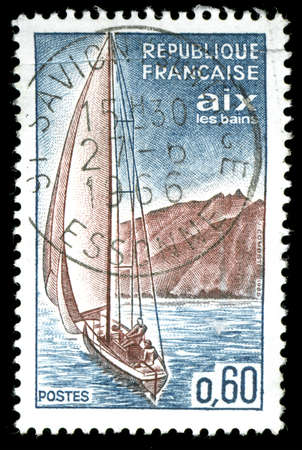 vintage french stamp depicting a sailing yacht sailing along a coastline photo