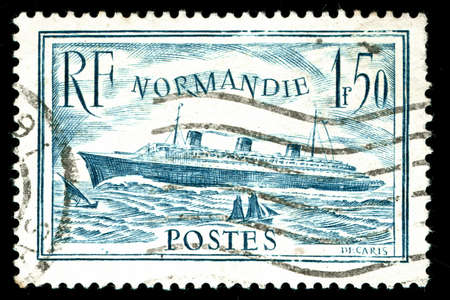 vintage french stamp depicting the launch of the passenger liner SS Normandie in 1932. she is considered to be one of the greatest Ocean liners ever built photo