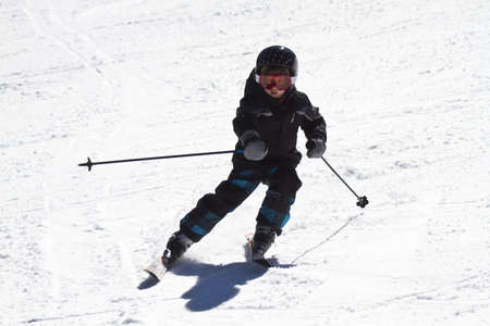 downhill skiing: young boy learning to ski Stock Photo