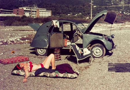 Originele vintage kleur dia uit 1960, jonge vrouw die op een strand met haar auto.