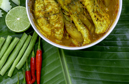 Yellow curry snapper fish with Lotus Stems, Southern Thai Spicy food and fresh vegetable in white dish on banana leaf / selective focus