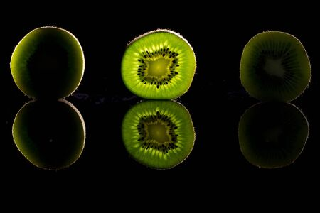 Kiwi on black glass, glass in transmitted light