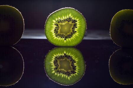 Kiwi on black glass, glass in transmitted light with light shimmer in the background Standard-Bild