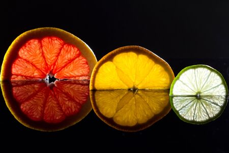Lime, orange and grapefruit with reflection in black glass as sunset