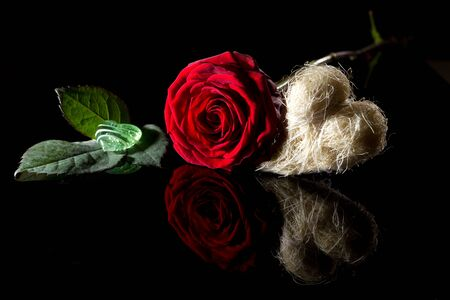 spiegelung: Rose auf schwarzem Glas mit Stroh und Glasherz  Spiegelung in schwarzem Glas vor schwarzem Hintergrund
