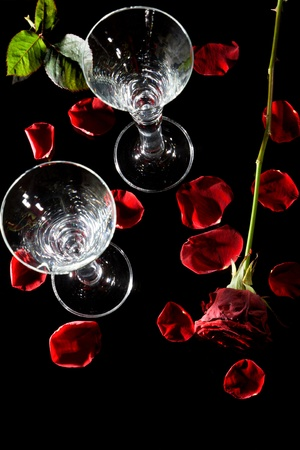 Champagne glasses, rose petals and roses on black glass