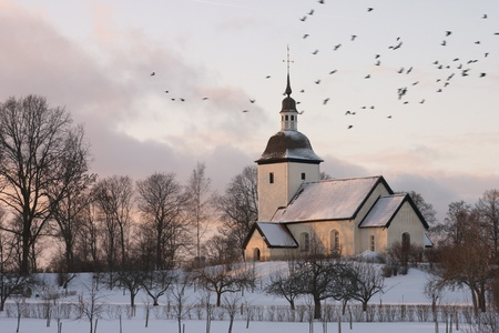 An old Swedish country church surrounded by a winter landscape at dusk with a flock of birds flying by  Stock Photo