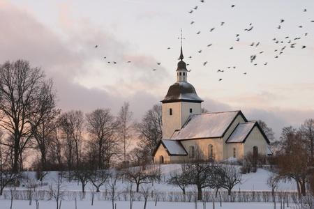 Een oude Zweedse land kerk, omringd door een winterlandschap in de schemering met een zwerm vogels vliegen door