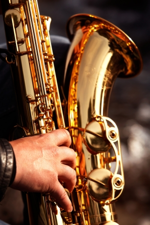 A hand is seen playing a saxophone  photo