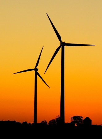 Two wind turbines in silhouette during sunset
