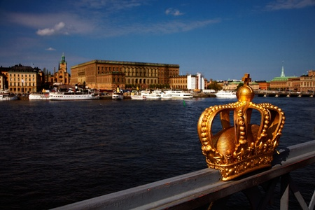 A golden royal crown on the railing of the bridge to Skeppsholmen with the Royal Palace and Old Town in the background. Location: Stockholm, Sweden - May 15, 2012 Stock Photo - 14654157