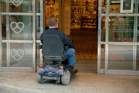 A man in a motorized wheelchair driving in through a door to the store Kringlan who are accessible to wheelchair users, in Sodertalje. Sodertalje, Sweden - July 16, 2012. Editorial