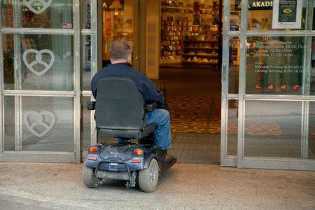 motorizado: Un hombre en una silla de ruedas motorizada de conducci�n a trav�s de una puerta de la tienda Kringlan que sean accesibles a personas con movilidad reducida, en S�dert�lje. S�dert�lje, Suecia - 16 de julio de 2012.