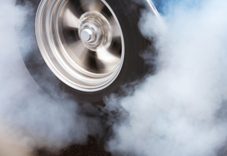 A car doing a burnout so that the tires spin smoke and smell of rubber
