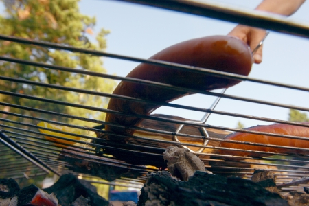 grill tongs sausage: Dogs Grilling on a rack over an open fire in the fireplace on a summer evening  A person with barbecue tongs visible handle the grill  Stock Photo