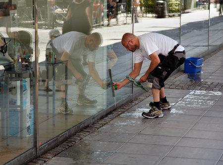 cleaning window: S�dert�lje, in Svezia - 20 luglio 2012: Un uomo pulire le finestre della vetrina del negozio in Kringlan S t e?.
