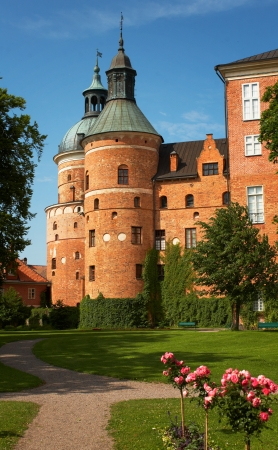 Part of Gripsholm Castle with a tower and park in Mariefred, Sweden. The castle is a royal palace built during the 1500s and is today a popular tourist destination.
