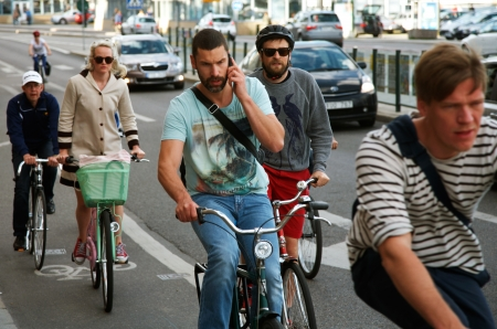 Stockholm, Sweden - June 20, 2012: A male cyclist without a helmet, talking on a mobile telephone among cyclists in traffic on tSkeppsbron  in Stockholm. Such like behavior results in less attention to traffic, which increases the risk of accidents. Editorial
