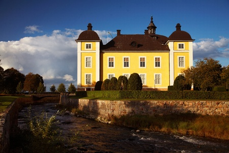 STROMSHOLM, SWEDEN: The yellow Swedish royal palace Stromsholm  (Str?olm) with blue sky with streams and moat in the foreground. Stromsholm palace is host to the annual horse race Swedidh Grand National Stock Photo - 14685827