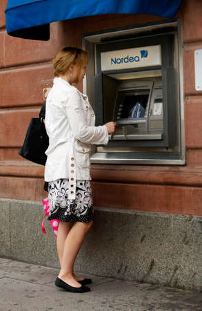 A young blond woman taking out money from an ATM belonging to Bank Nordea in the city of Uppsala, Sweden.