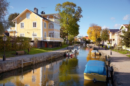 Trosa, Sweden - October 6, 2012: Moored boats in Trosa River in front of a yellow turn of the century building..  Stock Photo - 15850068