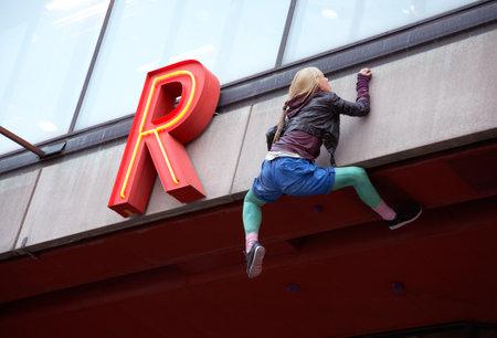 r image: Stoccolma, Svezia - 25 ottobre 2012: Particolare della (Casa della Cultura) Kulturhuset facciata con una bambola sospesa arrampicata sul muro.