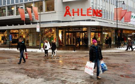 karlstad: Karlstad, Sweden - December 16, 2012: A person goes from Christmas shopping in ?lens with a bag marked with the store
