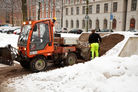 Stockholm Sweden - December 19, 2012: The driver of the mini-tractor with a snowplow on Valhallavägen loading sand for de-icing of walkways.