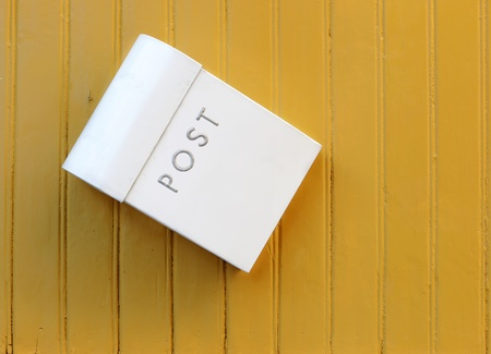 awry: The white mailbox hanging awry on a yellow painted wooden wall  Stock Photo