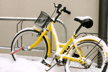 stated: Yellow bike in the snow correctly finds the bike rack and leaning against the wall