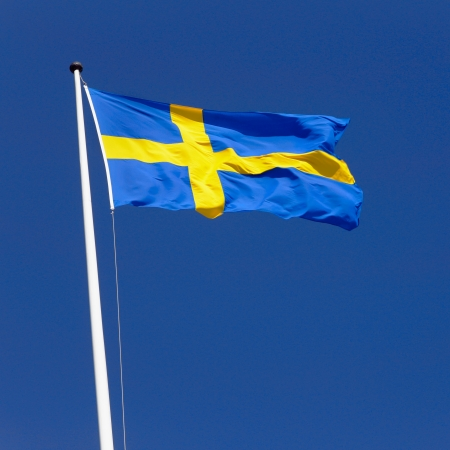 Swedish flag flies sunlit in the fresh wind on a flagpole against a clear blue sky  photo