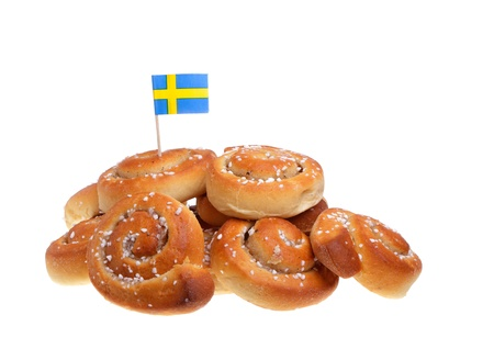 A pile of cinnamon buns with a Swedish flag on white background