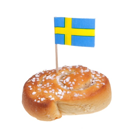 the swedish flag: A cinnamon bun with a Swedish flag on white background.