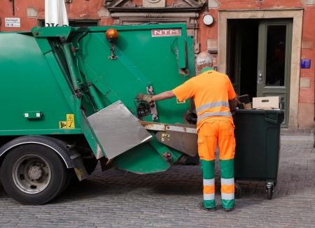 Stockholm, Sweden - June 18, 2013: A man in orange overalls empties garbage into a green garbage truck on the Main Square in the Old Town Editorial