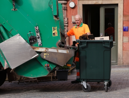 empties: Stockholm, Sweden - June 18, 2013: A man in orange overalls empties garbage into a green garbage truck on the Main Square in the Old Town Editorial
