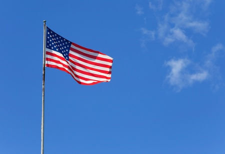 The American flag waves in the wind againts a blue sky  photo