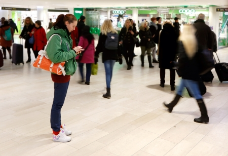 A young woman standing used a smsrt phone at the Centrsl station in Stockholm Sweden.