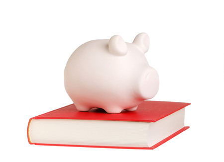 rewarded: A piggy bank standing on a closed book with red cover symbolizes that knowledge is rewarded, isolated on white background