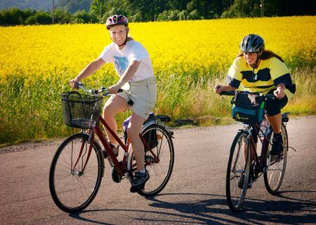 Two women bicycling at a narrow road at the Swedish countryside