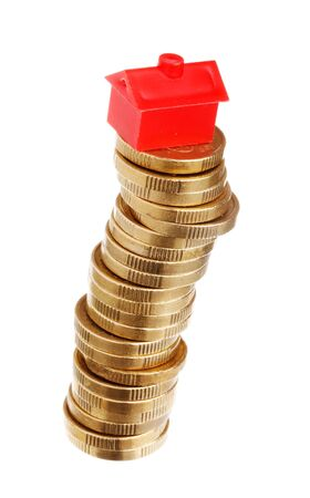 unstable: Red litle plastic house on top of an unstable stack of golden coins, isolated on white