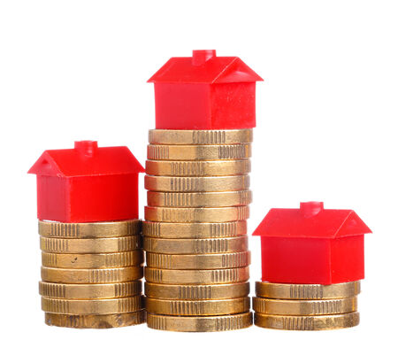 Red small houses on top of stacks of coins isolated on white  photo