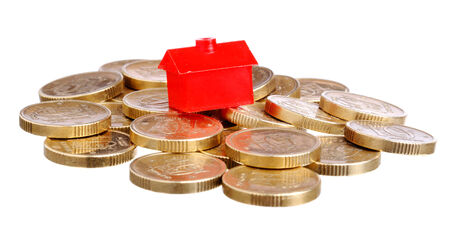 Red small house on top of a pile of coins isolated on white  photo