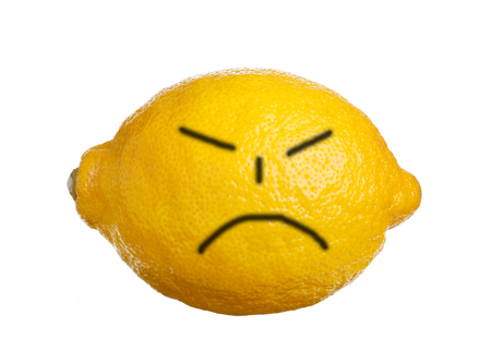 A face painted on a lemon expresses dissatisfaction, isloerad on white background