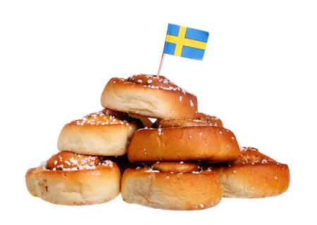 the swedish flag: PIle of cinnamon rolls with Swedish flag, isolated on white background  Stock Photo