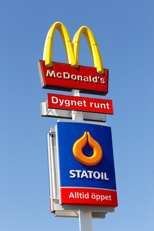Eskilstuna, Sweden - June 14, 2014  Signs at Vasterleden for the fast food hamburger restaurant McDonalds and the Statoil service station isolated on blue sky  Both are newer closed
